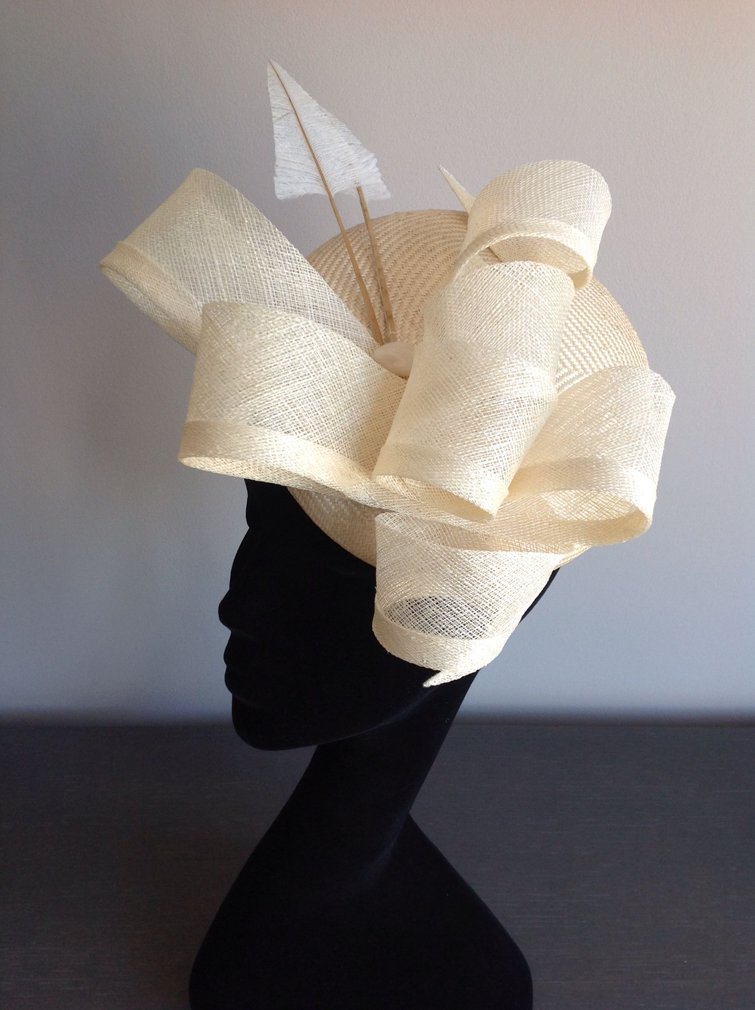 74334187f4ff5b Layers of oversized cream loops attached to a large round straw cocktail  base by couture milliner