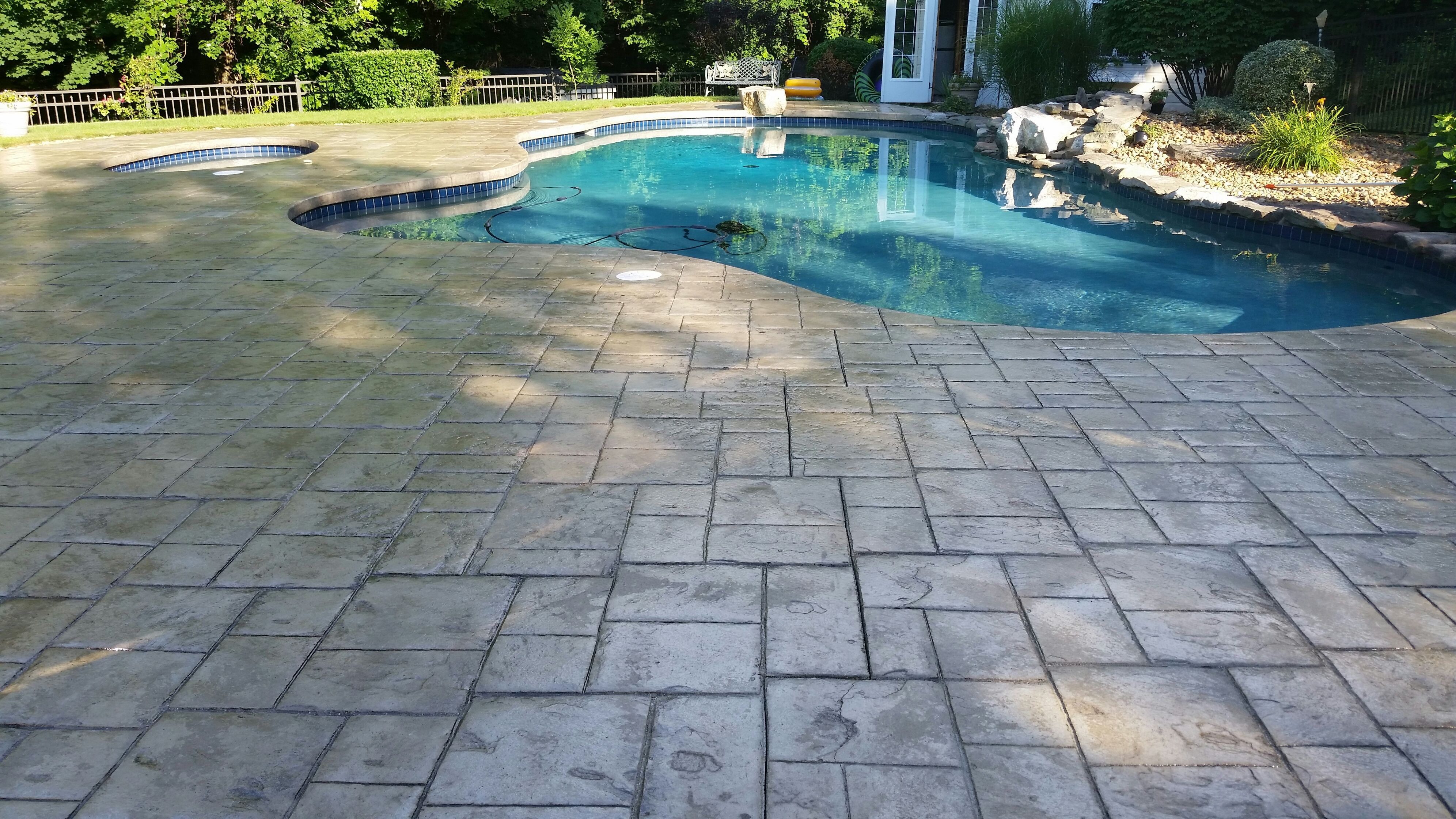 Stamped concrete pool deck sealed with a Foundation Armor