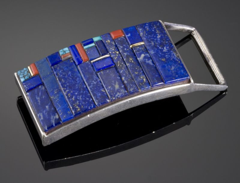 Sterling silver buckle with 14k gold accents inlayed with lapis, coral, and Lone Mountain turquoise by Charles Loloma. Measures 2 1/2″ x 1 1/4″.