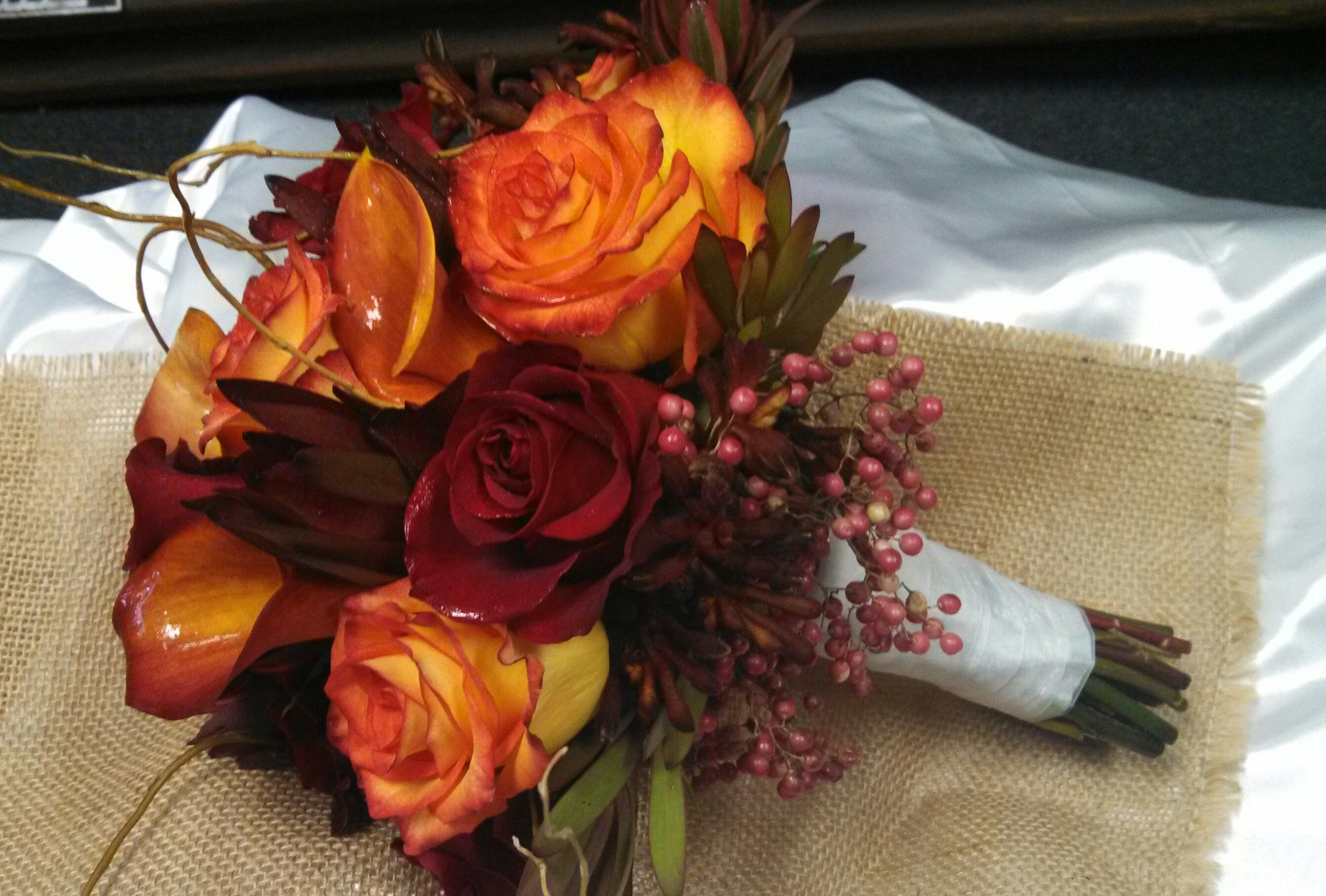 High Magic And Red Roses With Orange Cala Lilies Pepperberry Safari Sunset And Curly Willow Lily Wedding Wedding Flowers Cala Lily
