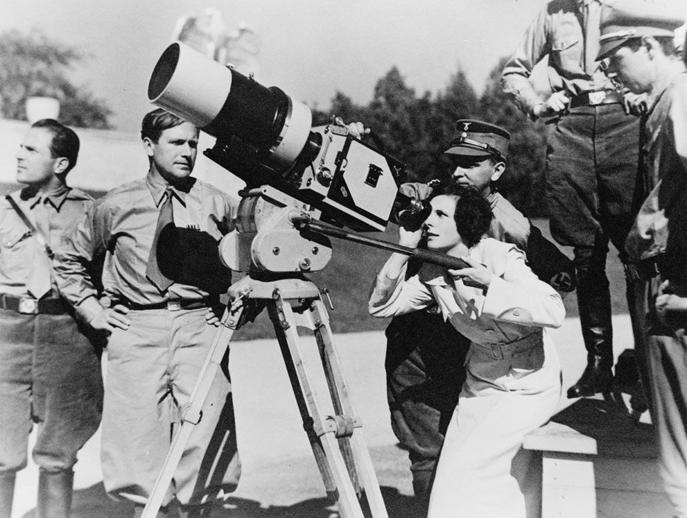 "Filmmaker Leni Riefenstahl looks through the lens of a large camera prior to filming the 1934 Nuremberg Rally in Germany. The footage would be composed into the 1935 film ""Triumph of the Will"", later hailed as one of the best propaganda films in history.  (LOC)"