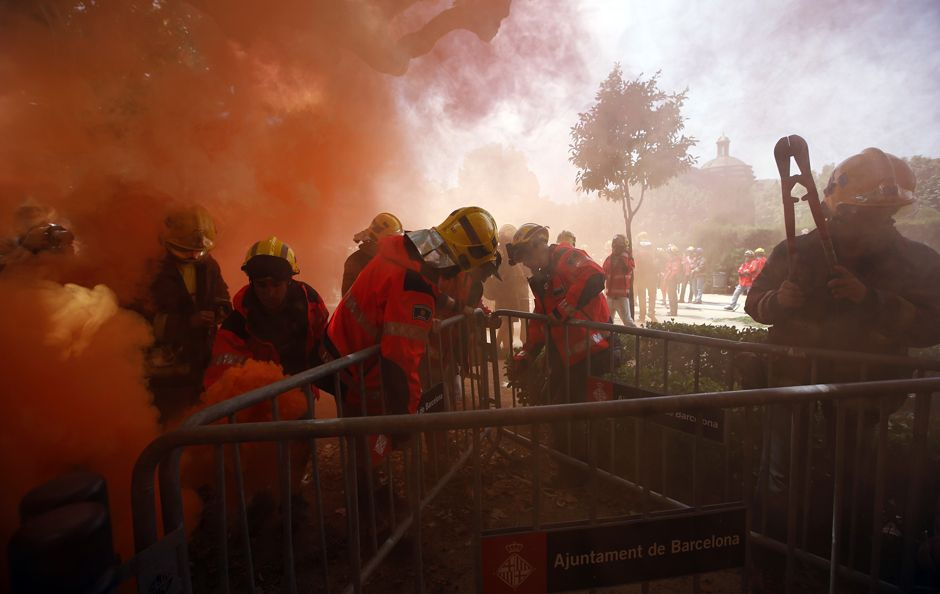 Fireman remove fences at the Catalunya's Parliament among red smoke during a protest against budgets cuts in Barcelona June 10, 2014. REUTERS/Albert Gea