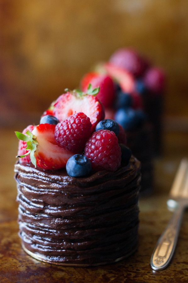 Rich chocolate cake is frosted with ganache and topped with berries for these mini double chocolate berry cakes