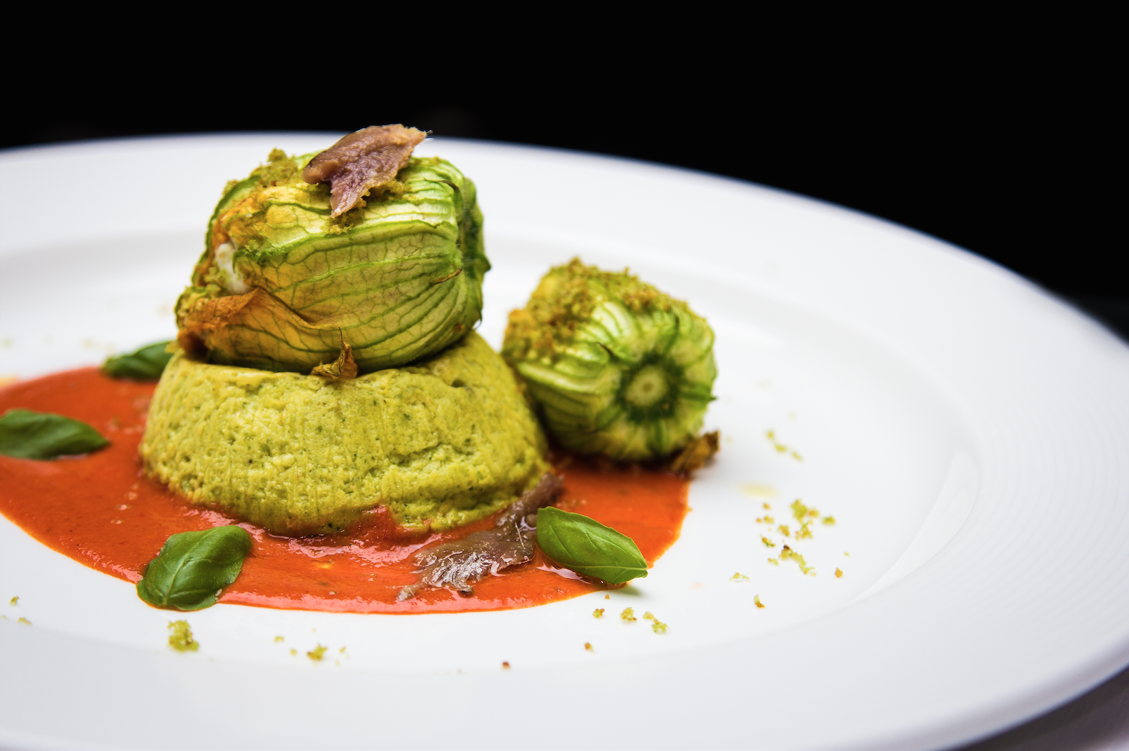 Sformatino di zucchine ai fiori imbottiti con ricotta e basilico, salsa ai peperoni arrostiti e acciughe del Cantabrico