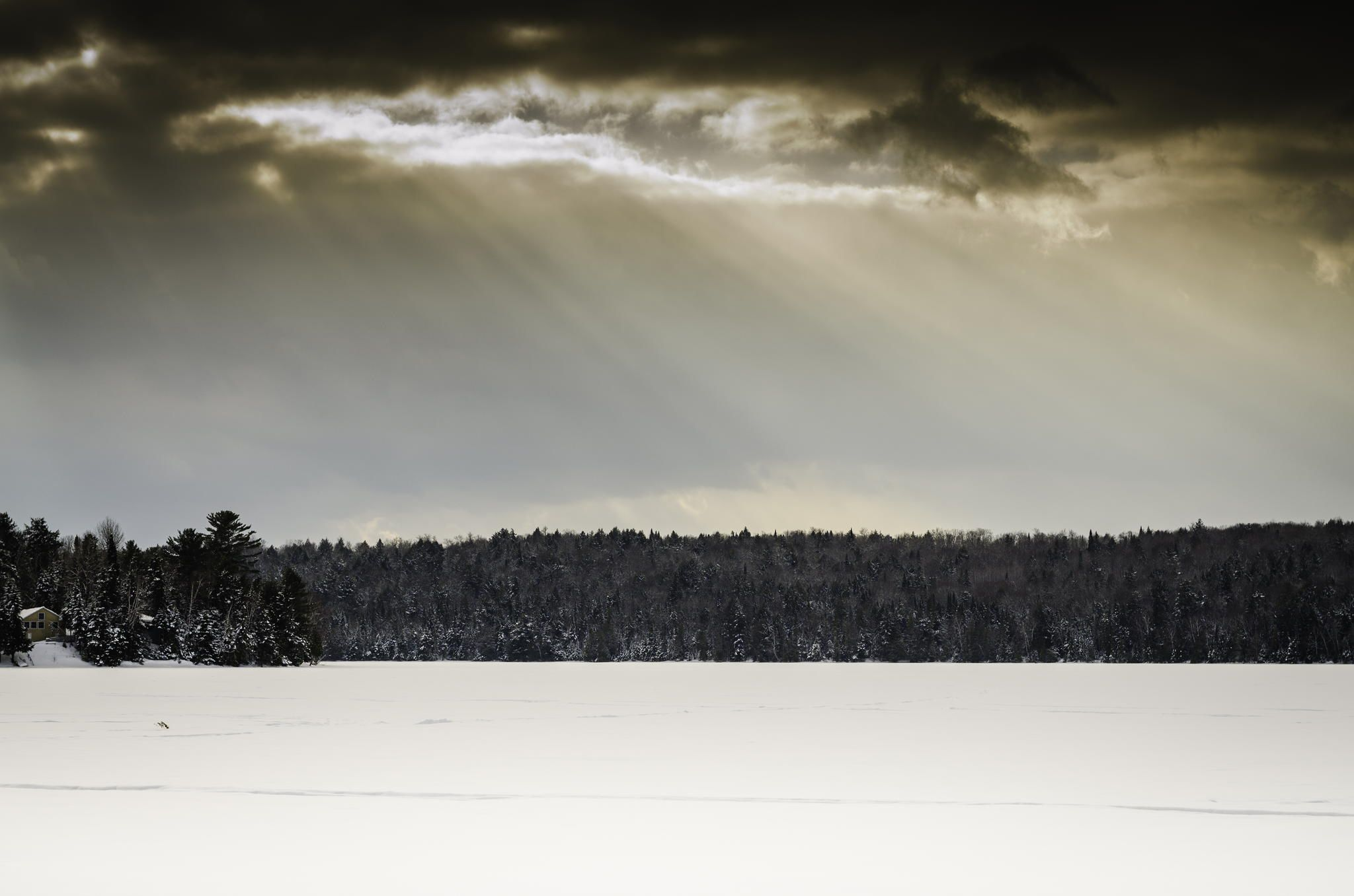 Rays of sunlight stream down from the clouds over a snow covered lake in Aroostook County.  A cottage can be seen across the lake tucked in amongst the snow covered trees.