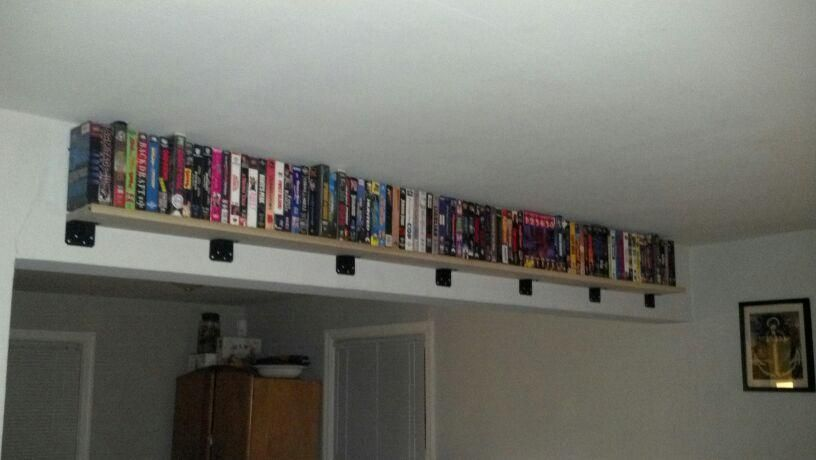 New shelf to display our VHS collection. A poplar 1x6 and 7 l-braces we spray painted black.  Great use of that 'unusable' beam in the middle of our room!