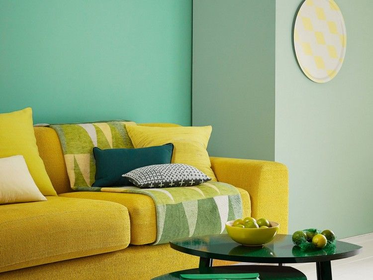 Wandfarbe Grün im Wohnzimmer mit gelbem Sofa kombiniert