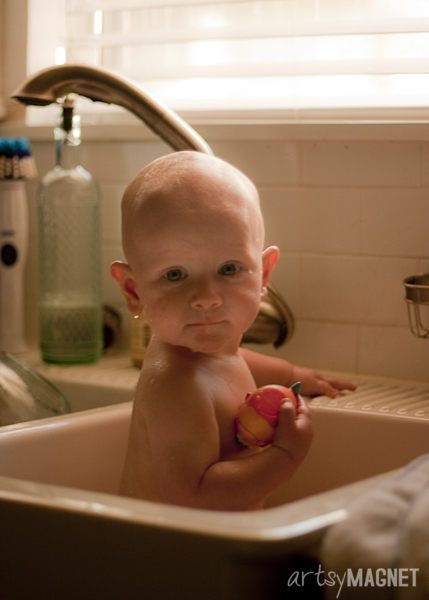 Baby bathing in the kitchen sink. \