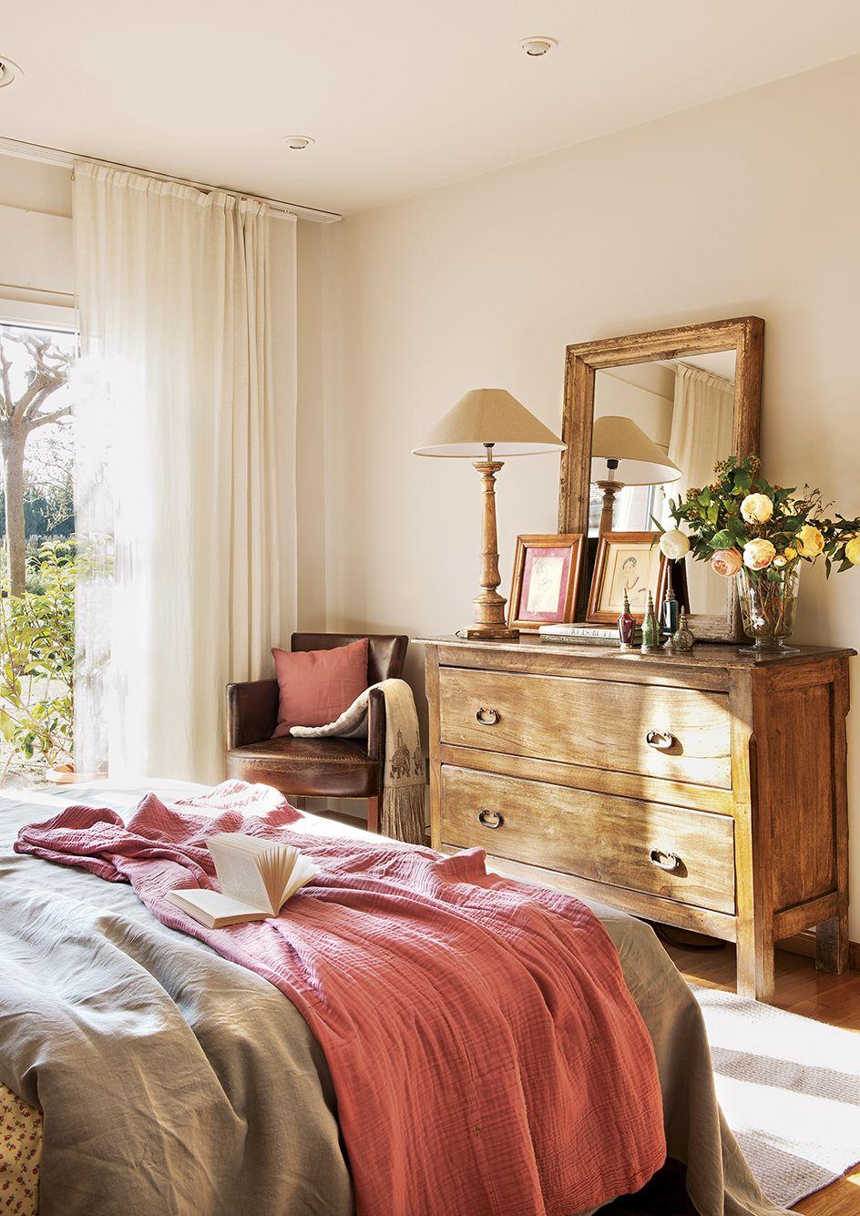 Dormitorio en tonos cálidos con banqueta, butaca y armarios con ...
