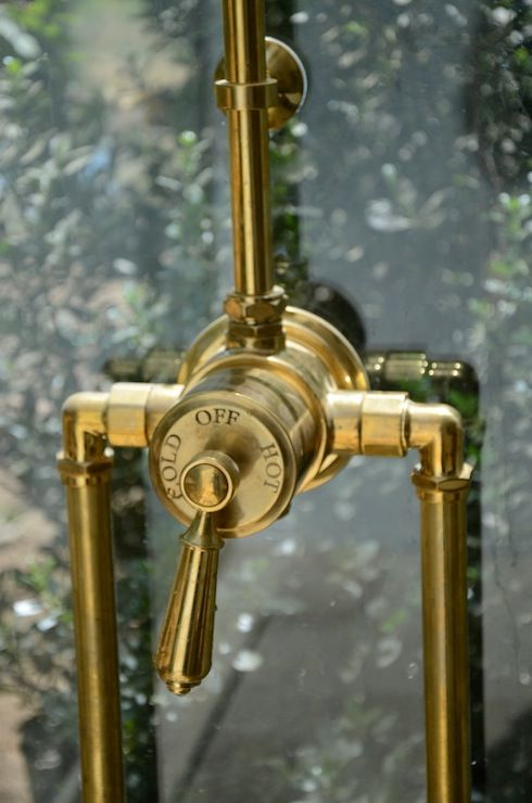 Photo of Beautiful glass shower exposed with unpainted brass waterworks …