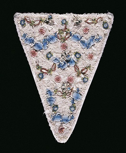 stomacher c.1750. Patterned silk ttrimmed with ribbon, fly fringe and lace, paper backing