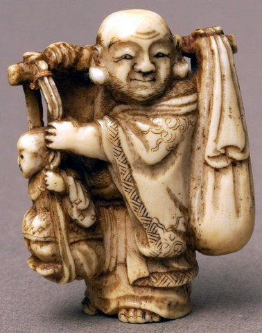 Ivory netsuke depicting a man carrying a branch over his shoulders with a sack tied to one end and a child standing on a rope at the other end.