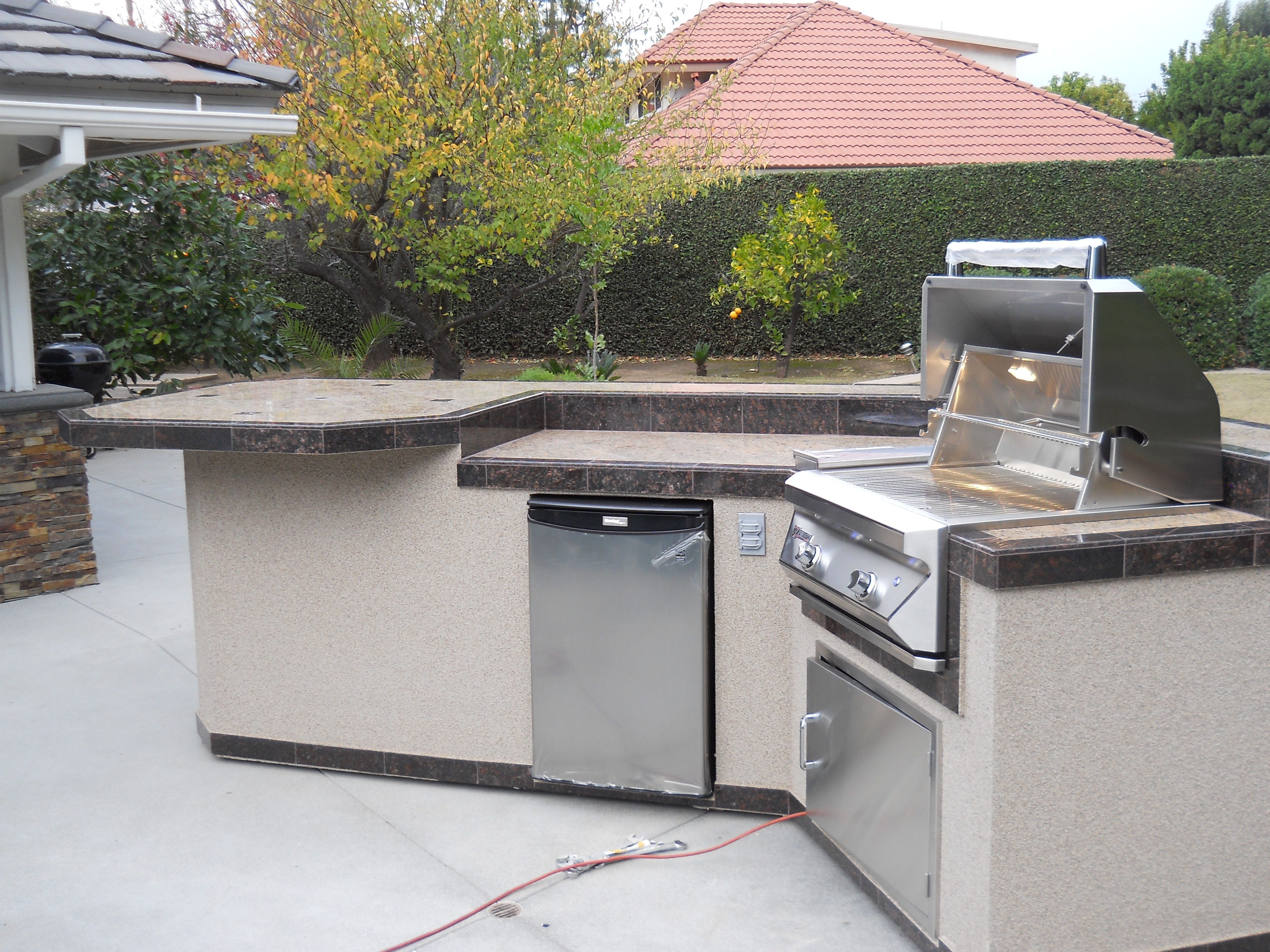 Custom built outdoor kitchen delivered to orange county ca built in grill mini fridge recessed lights access door bar seating