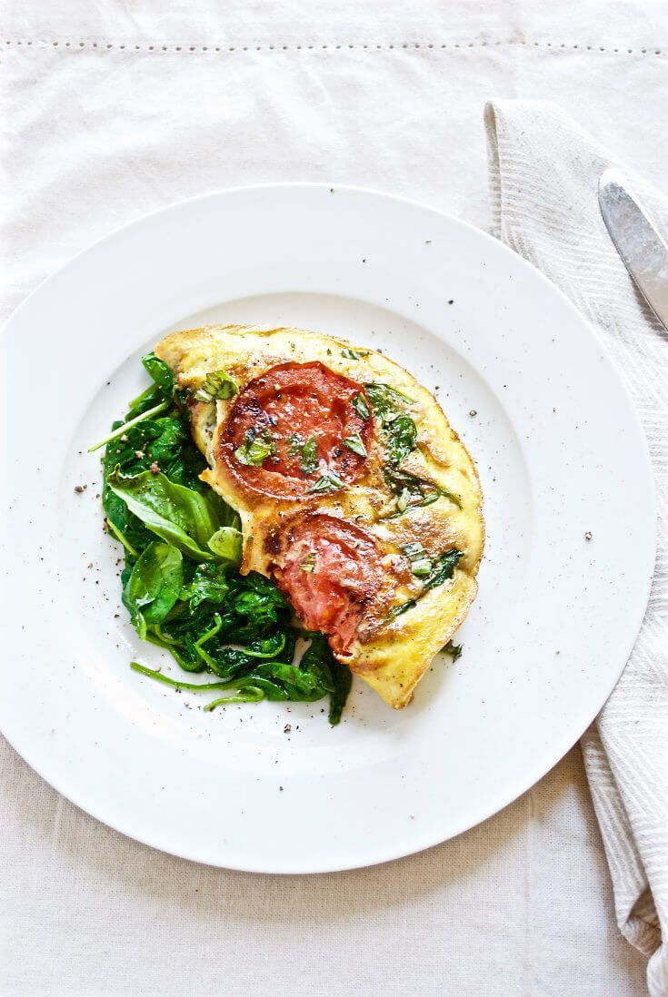 Caprese omelet made studded with juicy tomato jewels and warm, gooey buffalo mozzarella hiding inside. Served with sauteed spinach and basil.