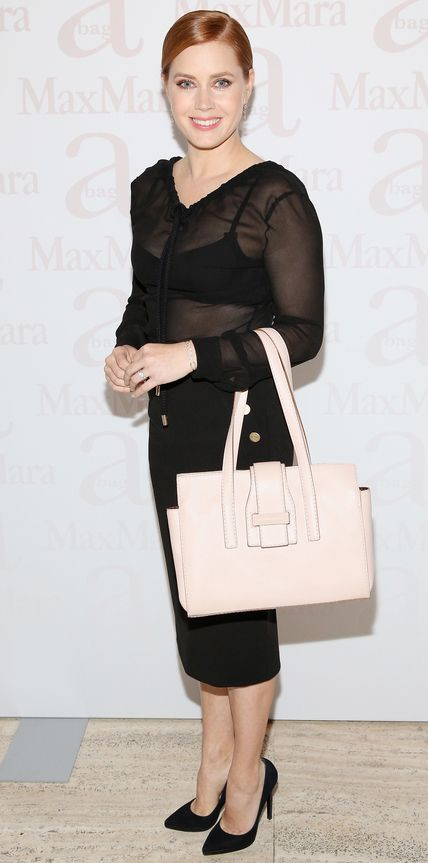 As the face of Max Mara's spring 2016 accessories campaign, Amy Adams was honored at a fete, in which she wore a sheer black blouse tucked into a demure midi-length pencil, with a blush pink tote, all by Max Mara.