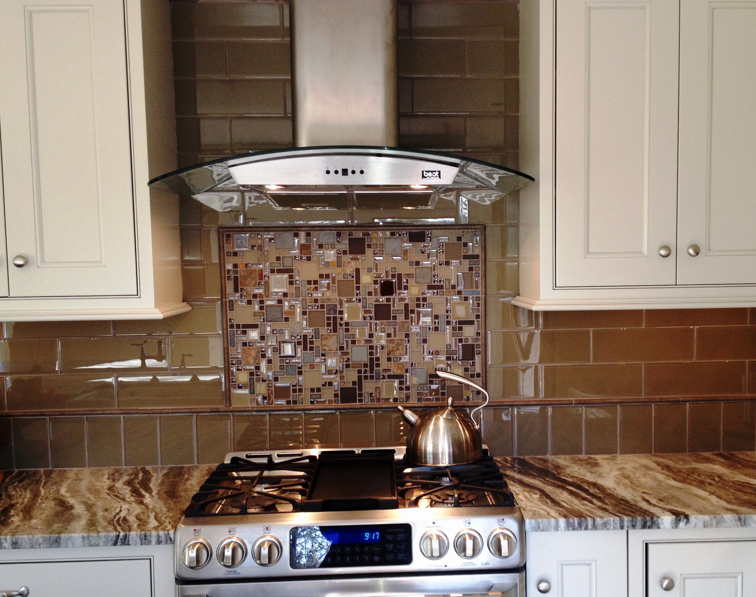 Glass tile backsplash with framed mosaic tile insert over the glass tile backsplash with framed mosaic tile insert over the stove brown fantasy quartzite countertops dailygadgetfo Images