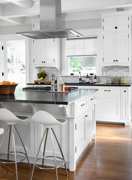 Gourmet Kitchen Features A Stainless Steel Vent Hood Suspended Over A White  Center Island Adorned With