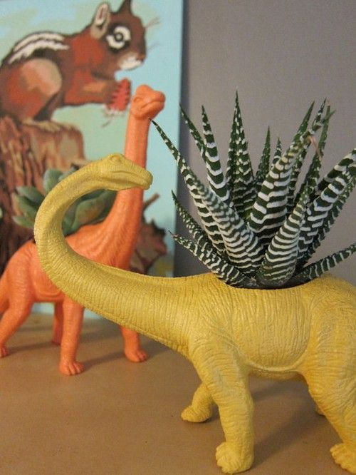REUSE DINOSAUR ..  Using toys that pot, so why not! I was so eager craft after seeing these pictures and all you need to do your own playful pots are: A plastic figurine , large drill , color and a flower