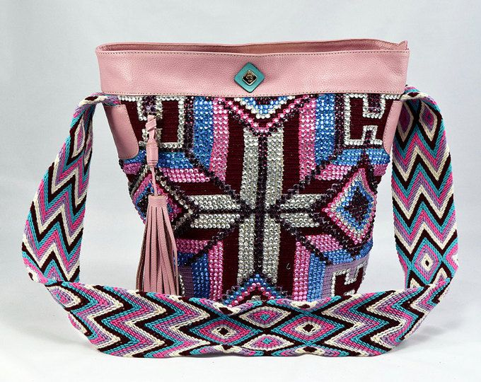 This is an original Mochila Wayuu bag which has been decorated with over 2000 crystals and assembled in 100% genuine leather and lined inside. The strap is also made with genuine leather. This Luxury Mochila Bag is handmade. It has taken almost 3 weeks to wave and few days to adorn. It is a great product for summer, to wear in cities, beach and festivals.