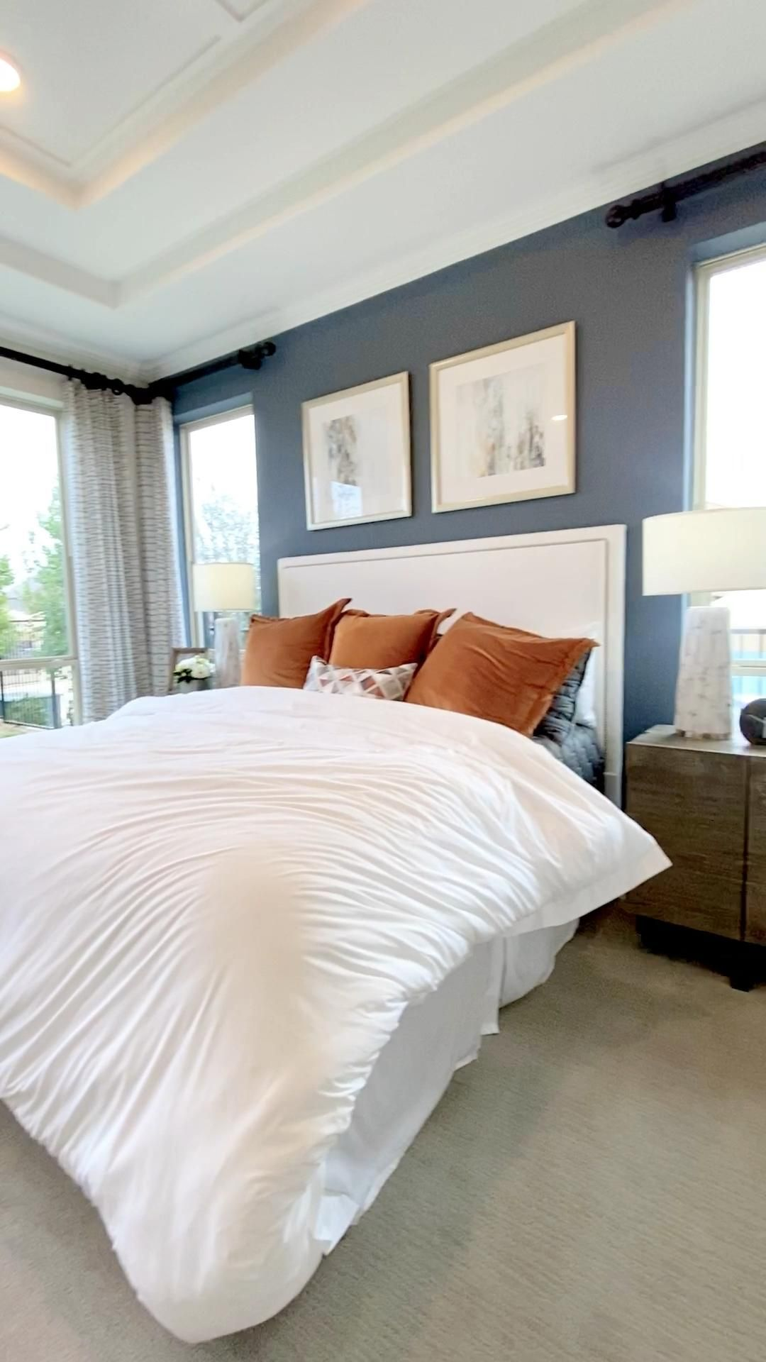Beautiful owners suite with blue feature wall, white bedding, and seating area.  Click to see more model home decor inspiration photos... THE DECORATING COACH