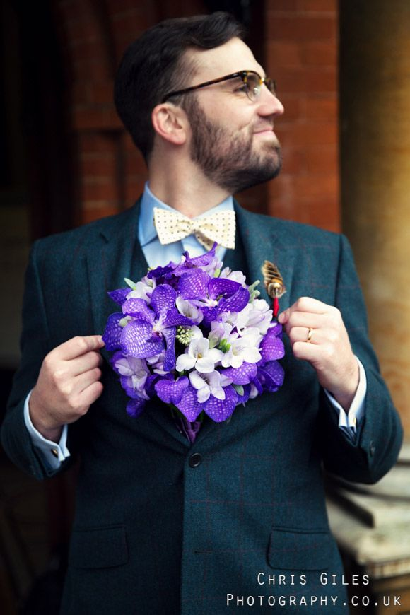 Groom in Tweed doing a superman impression with flowers from Myrtle and Mint florists