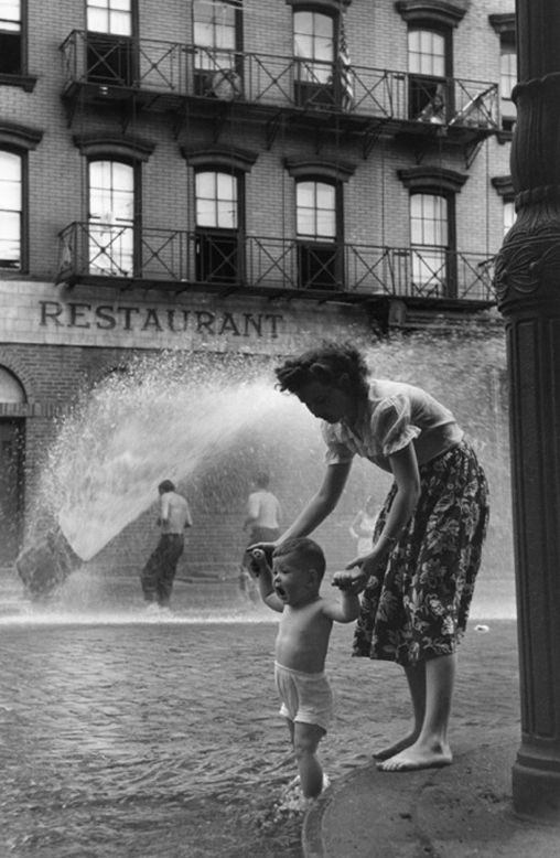 Mother and baby in gutter. © Ruth Orkin #black_and_white #Photography