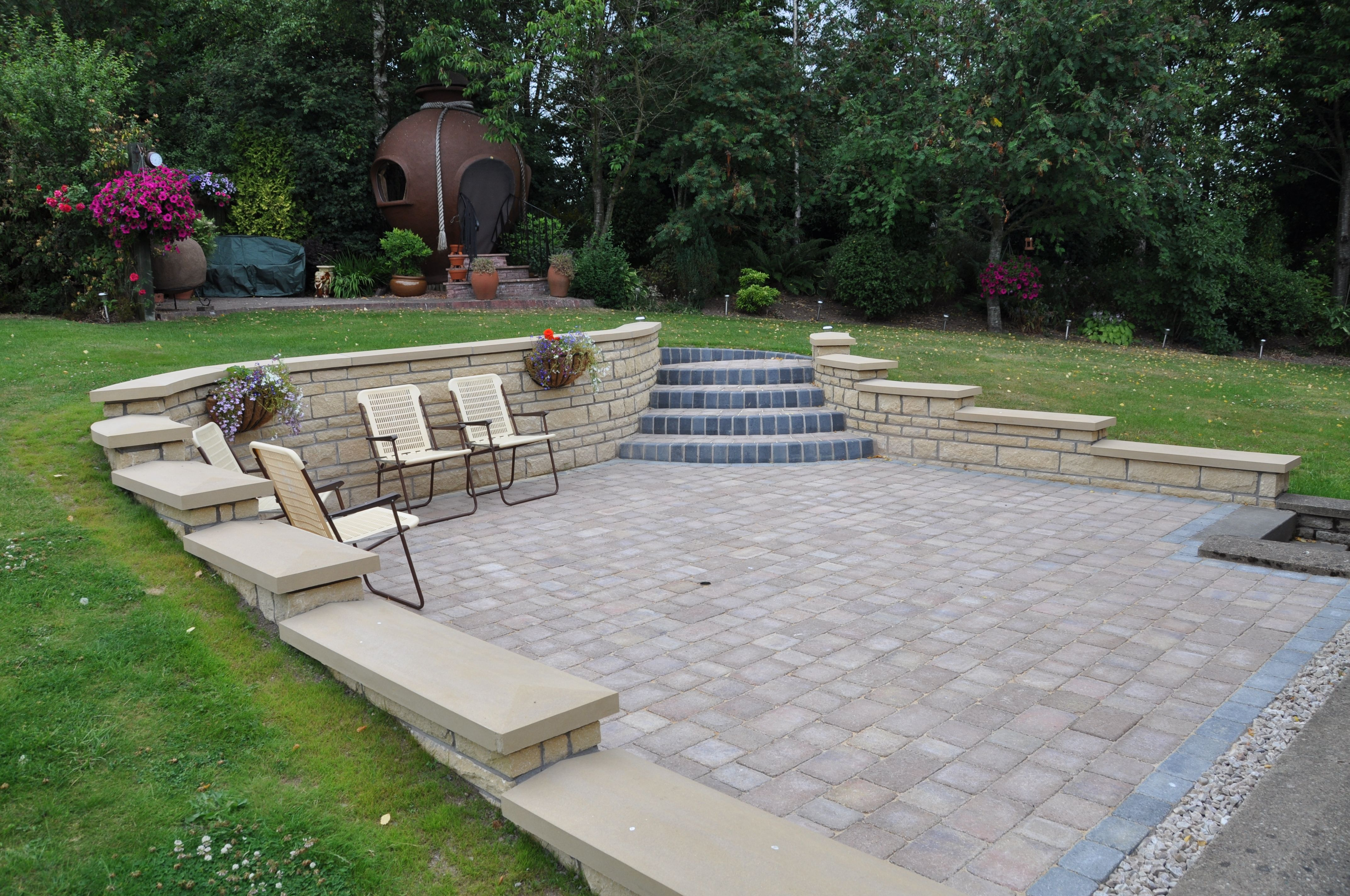 Curved patio with retaining wall and contrasting steps.   Backyard ...