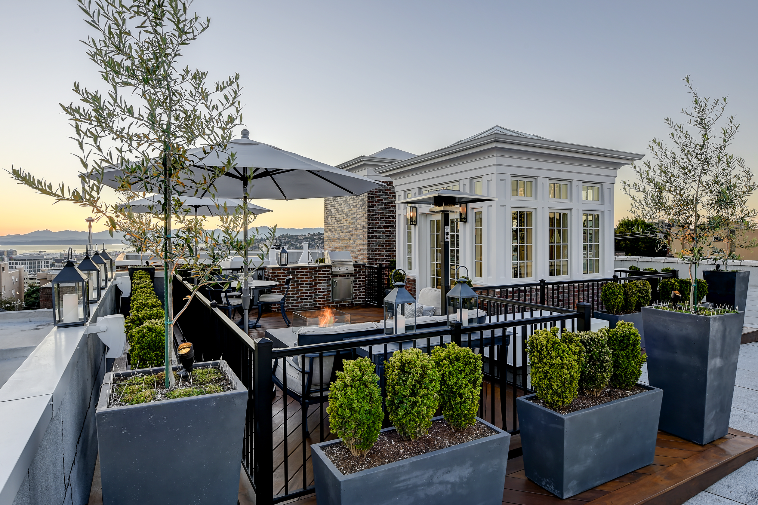 The Sun Sets Behind The Mountains And A Space Needle View From This Rooftop Deck Classicalroof Rooftop Patio Design Roof Garden Design Rooftop Terrace Design