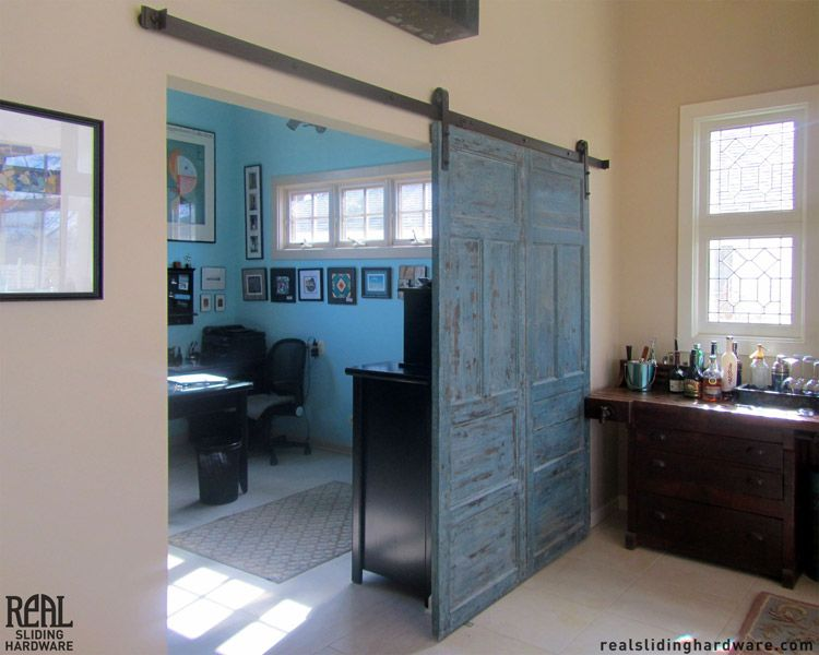 This blue barn door separates an office space and entertainment