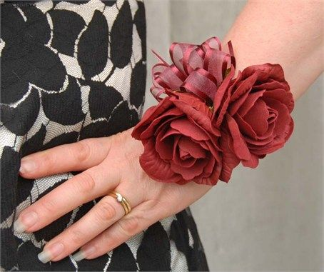 A stunning artificial Wedding wrist corsage, with two burgundyIsabel roses and a small ivy leaf underneath.Mixed sheer organza burgundy bow  and a matching burgundyribbon to tie to the wrist. MeasurementsWidth:- 4.5 inchesLength:- 4  inches Artificial wrist corsage, suitable for any of the wedding party. For thebride not wanting to carry her bouquet all day, bridesmaids, Mothers of the Bride and Groom and guests.Or for a prom corsage or a special party.