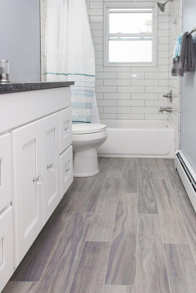 Light Gray Tile Bathroom Floor With White Bathtub Surround