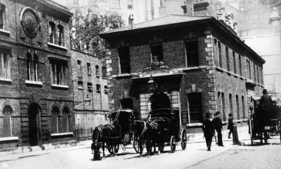circa 1875: On the left, Scotland Yard, in the centre with horse drawn cabs outside is the Public Carriage Office