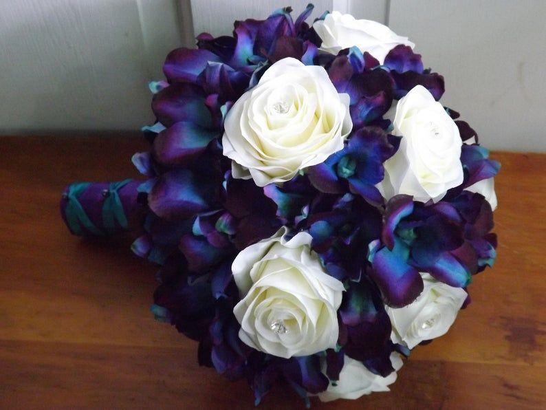 Blue purple galaxy dendrobium orchids and white cream rose