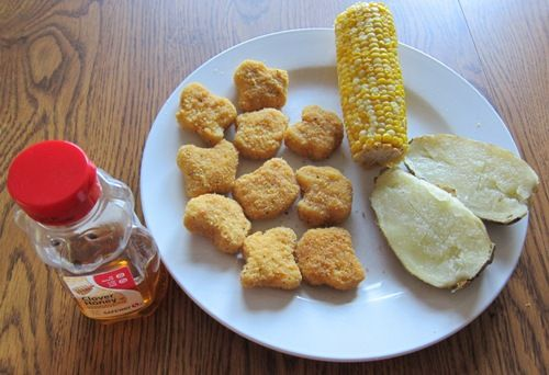Microwave Dinner Of En Nuggets With Corn On The Cob And Baked Potato