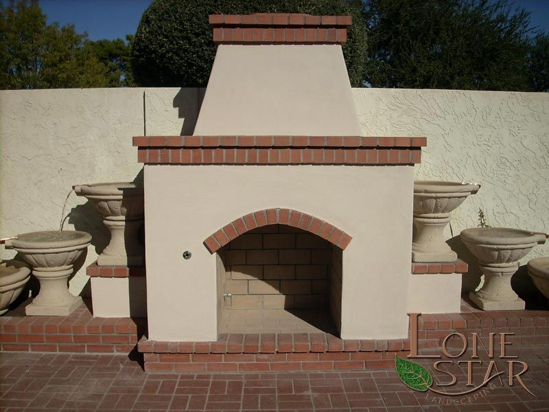 Outdoor Fireplace With Red Brick Trim And Water Feature In Phoenix