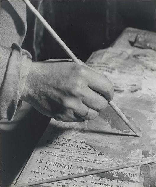 """Conversations with Picasso: Picasso painting on a newspaper in his studio on Rue des Grands Augustins"". 1939. Paris, France. Brassaï."