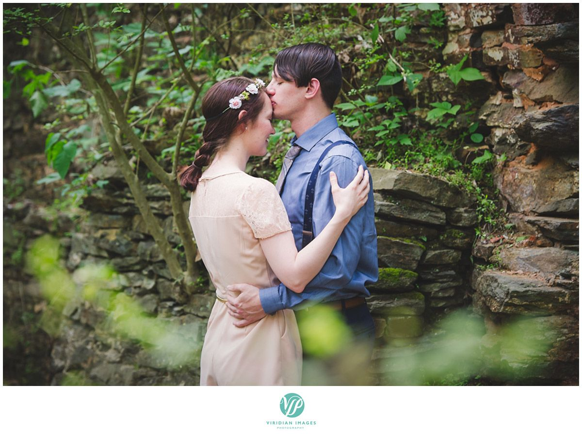 Enchanted kiss on the forehead by groom to be with the rocky outdoors behind