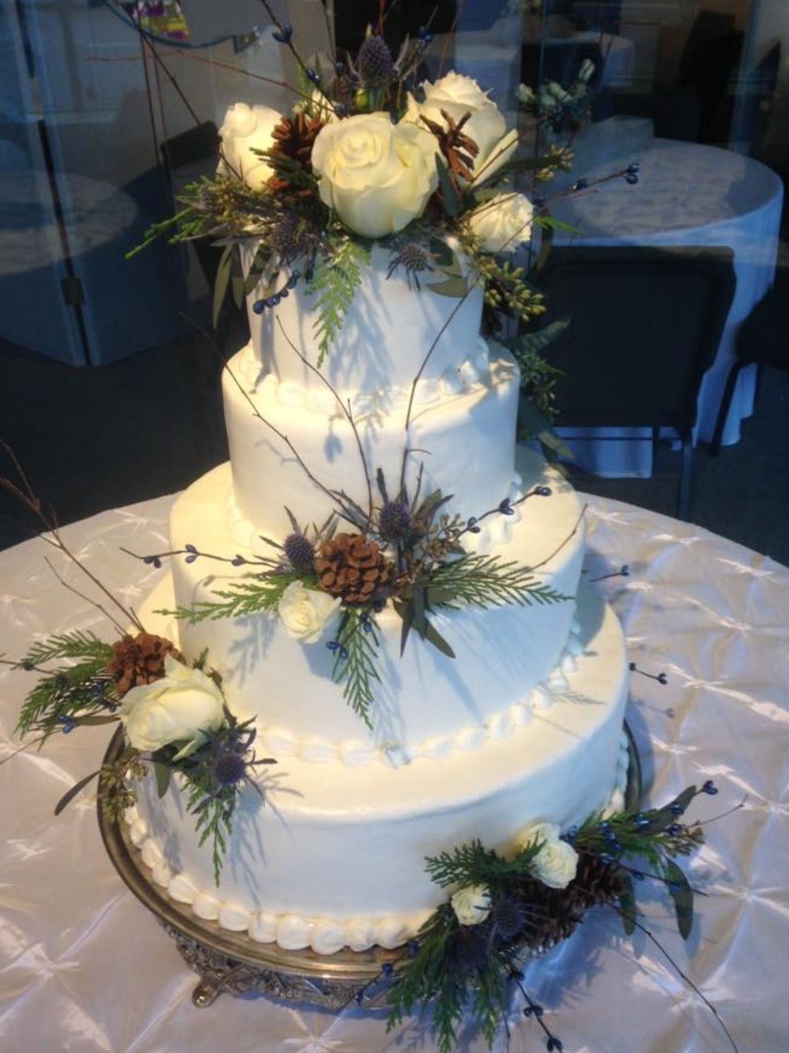 Simple smooth iced cake adorned with berries, pine cones and winter greens.cake designed by Flowers by the Bunch