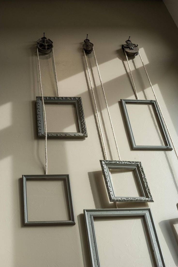 Photo of Hanging frames attached to a pulley system tie the upstairs and downstairs livin…
