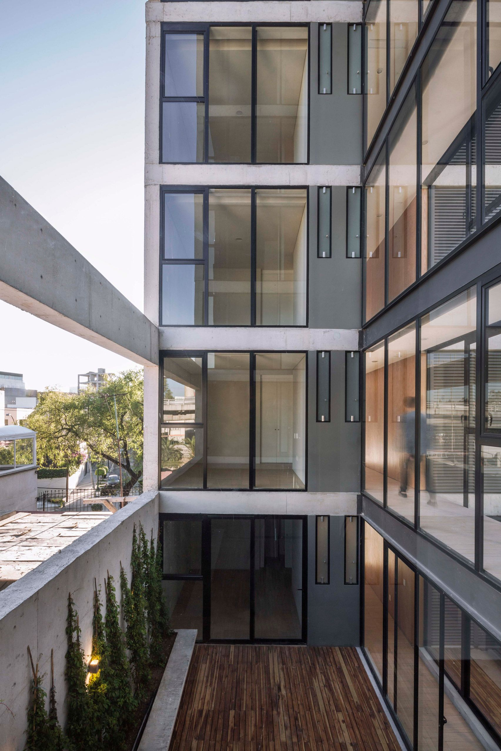 Each Apartment In This Concrete And Glass Block In Mexico City Features A  Balcony Lined With Sliding Glass Doors That Connect It To An Indoor Living  Space.