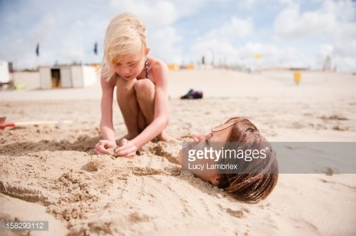 Young girl shaping a sand mermaid after burying her mother in sand at the beach.