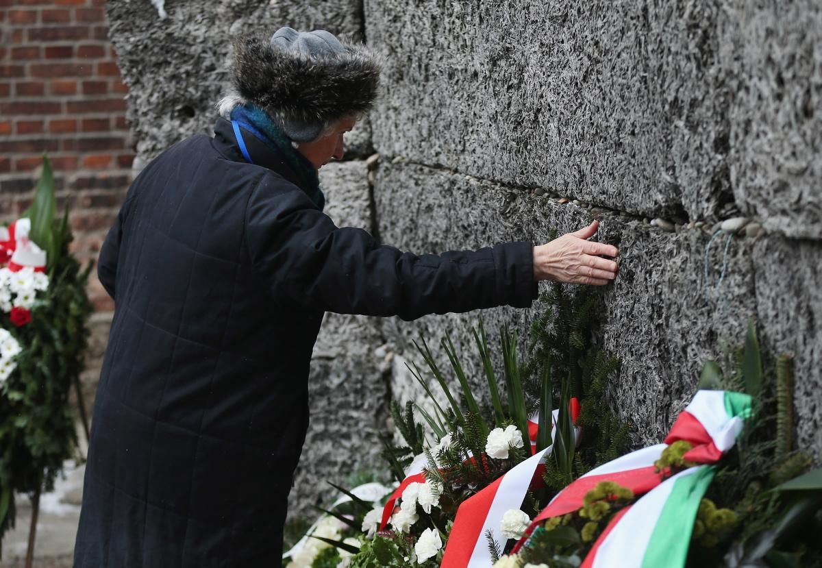 """A member of an association of Auschwitz concentration camp survivors lays her hand at the execution wall at the former Auschwitz concentration camp in Oswiecim, Poland on Jan. 27, 2015. The """"wall of death"""" was used to beat and torment prisoners before ultimately killing them. It estimated that at least 20,000 people were killed at this very wall alone."""