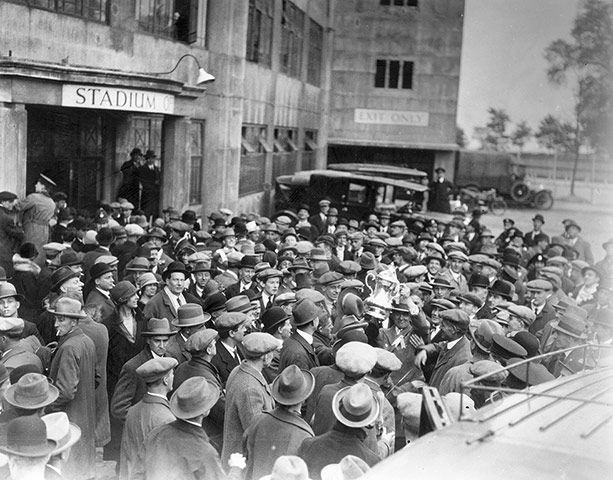 Bolton Wanderers supporters surround Bolton Wanderers captain, Joe Smith, as holds the FA Cup aloft as the victorious Bolton team try to leave Wembley Stadium after the 1926 FA Cup final victory over Manchester City.
