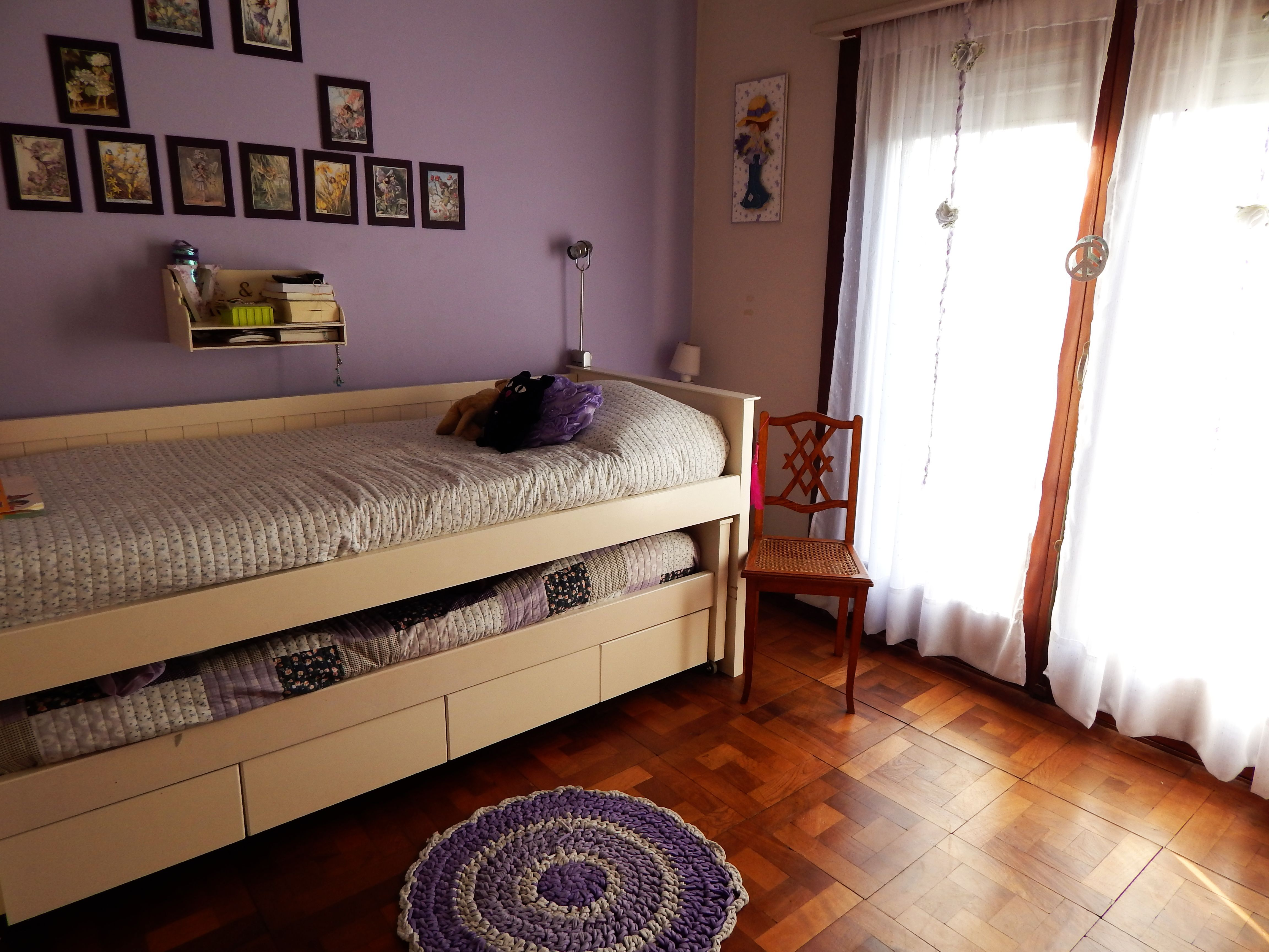 """Habitación de niñas. La cama nido es muy práctica para ahorrar espacio (y cómoda para tender). Los cuadritos en la pared son illustraciones vintage de """"Flower Fairies"""" de Cicely M. Barker."""