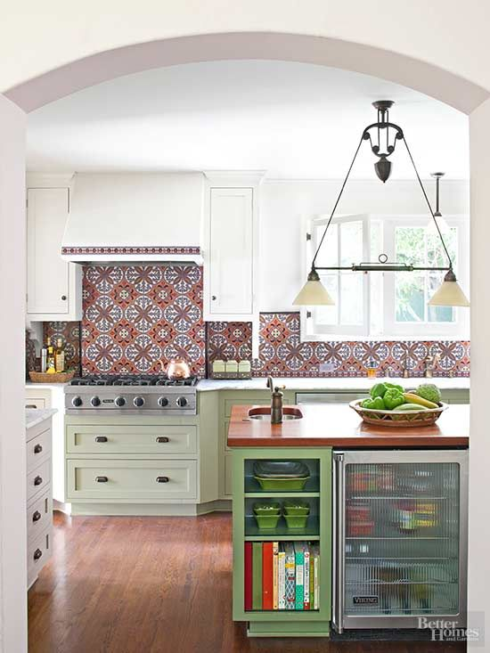 This may be our favorite kitchen makeover yet. See how this dated kitchen got a major overhaul with a beautiful tile backsplash, green cabinetry and stainless steel appliances. This open floor plan perfectly fits an island with built-in shelves and plenty of countertop space.