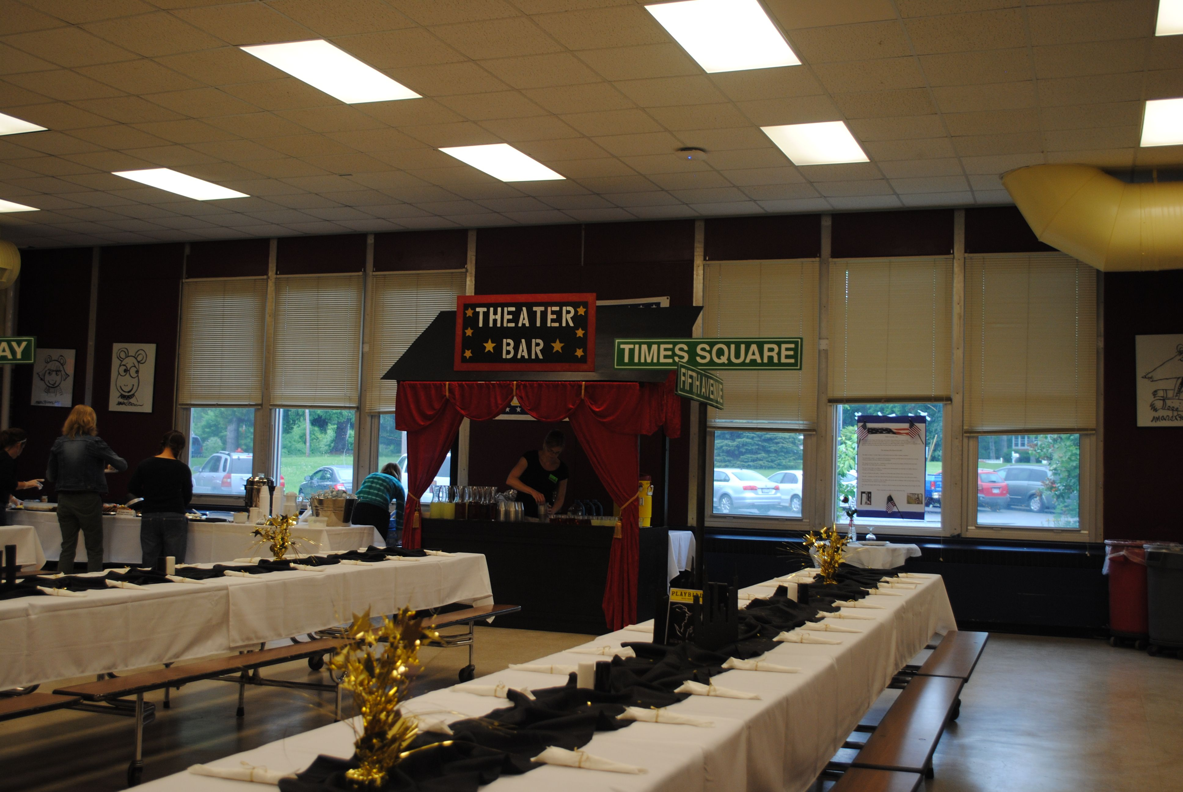 Tables with black runners and Broadway themed centerpieces