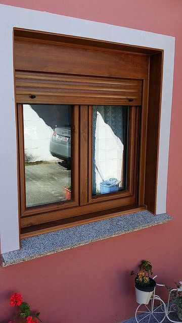 Ventana pvc color roble dorado con persiana bajando por el for Ventanas pvc color madera