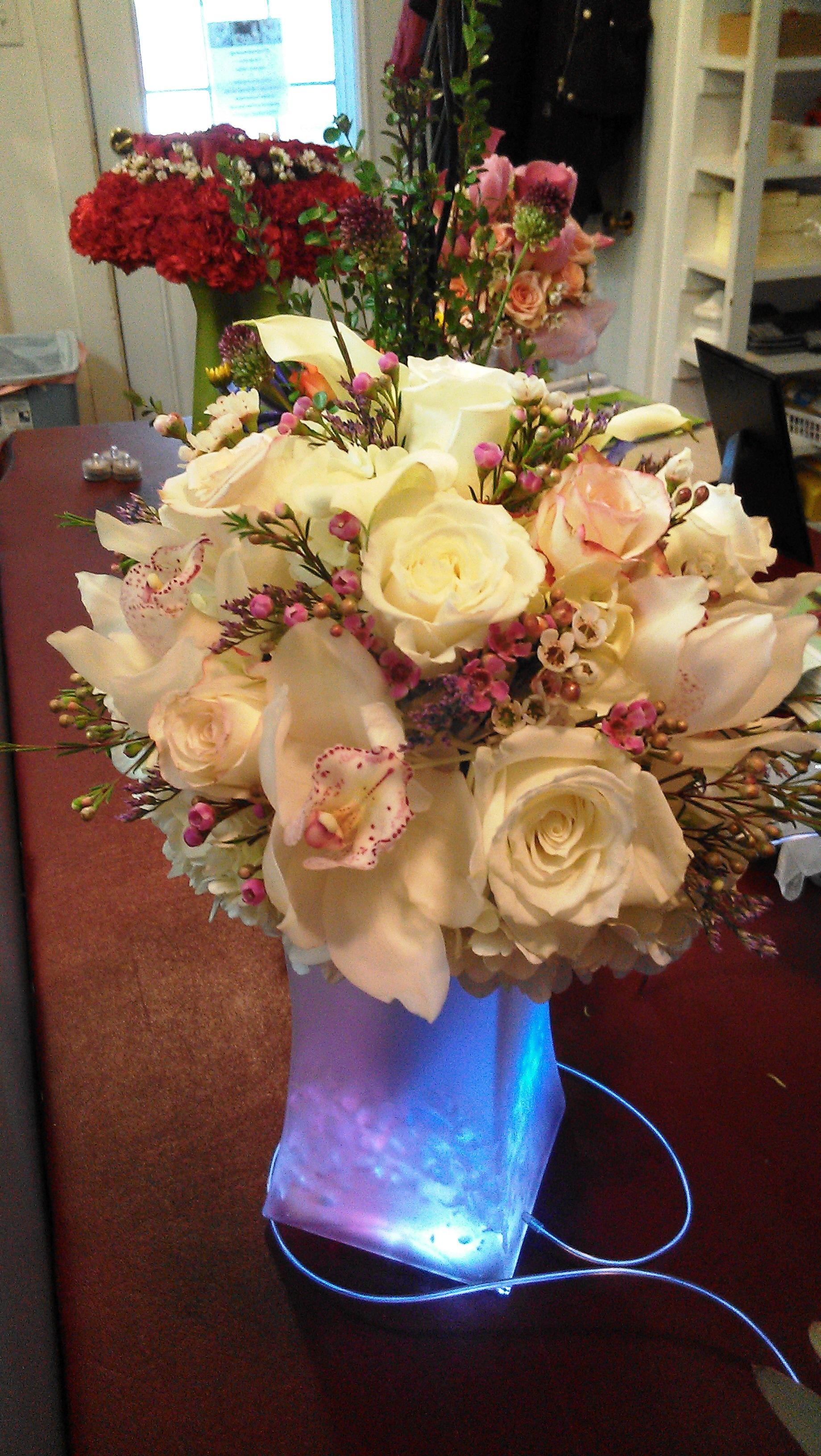A bouquet of white roses, orchids, and pink waxflower. The bouquet is sitting in a frosted vase filled with California crystals and lit with multicolor submersibles.  See more wedding bouquets, centerpieces, and more at www.jeffmartinsweddings.com