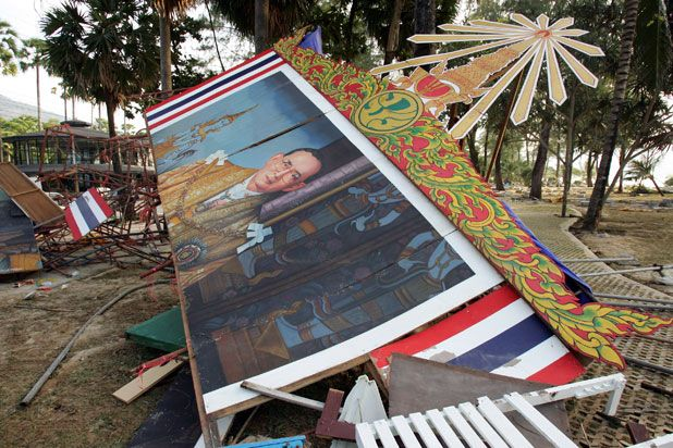 A painting of King Bhumibol Adulyadej is toppled one day after the 26 December tsunami struck along Patong Beach, one of the worst hit provinces of Phuket, Thailand, 2004, photograph by Paula Bronstein. The King's grandson, Bhumi Jensen, died in while riding a personal watercraft near his hotel in Khao Lak when the wave over took swiftly overtook both sea and land, one of nearly 228,000 people killed in the most deadly tsunami in recorded history.