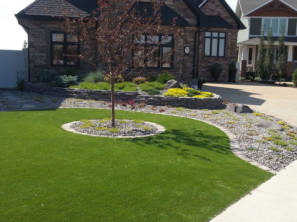 minimal maintenance front yard with artificial turf and a rock wall foundation bed